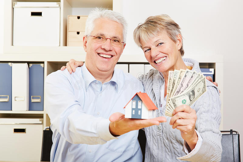 Senior couple with house and dollar stock photos