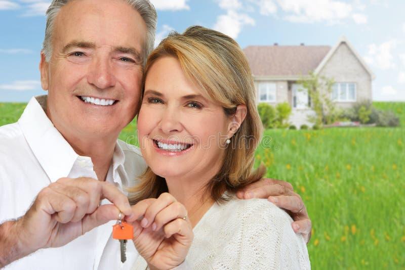 Senior couple with house key. Smiling happy elderly couple holding house key stock photography