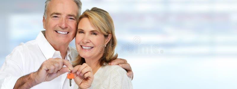 Senior couple with house key. Smiling happy elderly couple holding house key stock images