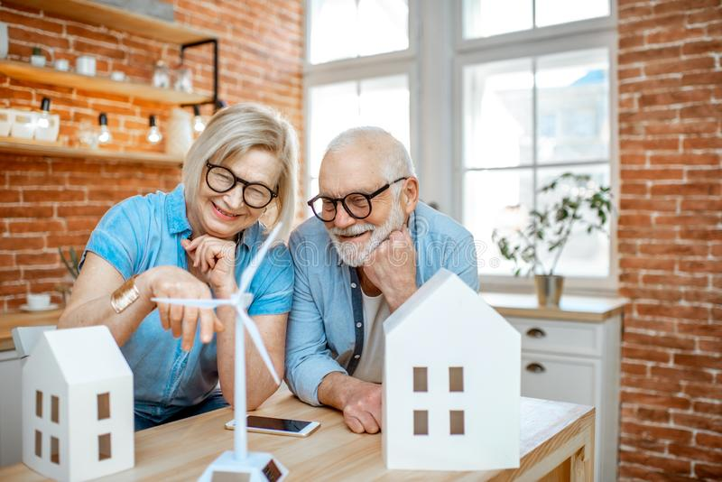 Senior couple with house models and toy wind turbine at home royalty free stock photo
