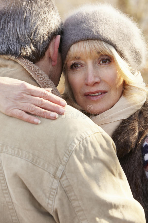 Senior couple hugging outdoors in winter royalty free stock photography