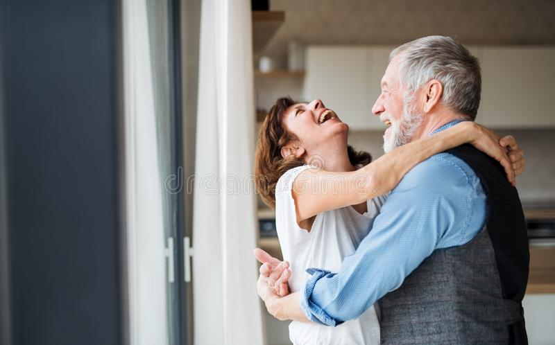 A senior couple indoors at home, laughing and hugging. A senior couple standing indoors at home, laughing and hugging royalty free stock photo