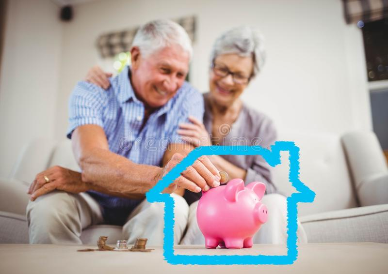 Senior couple insert coins in piggy bank against house outline stock images