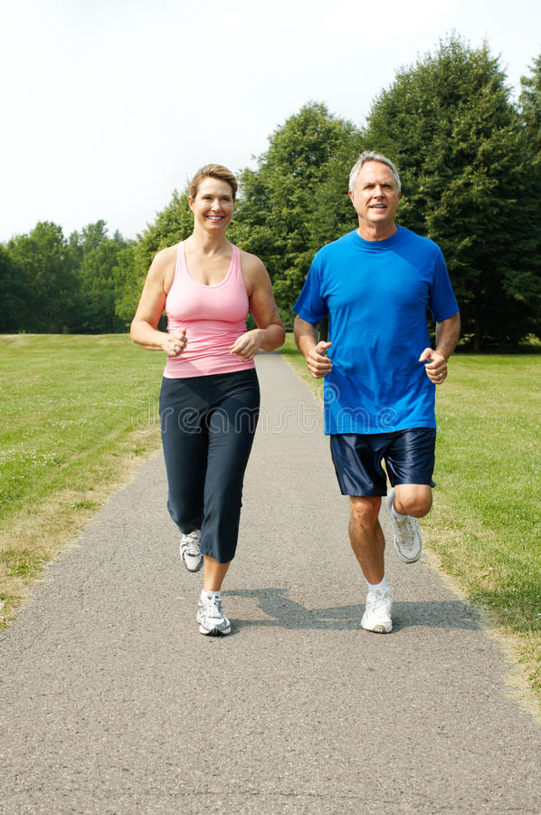 Senior couple jogging. Happy elderly senior couple jogging in park stock photography