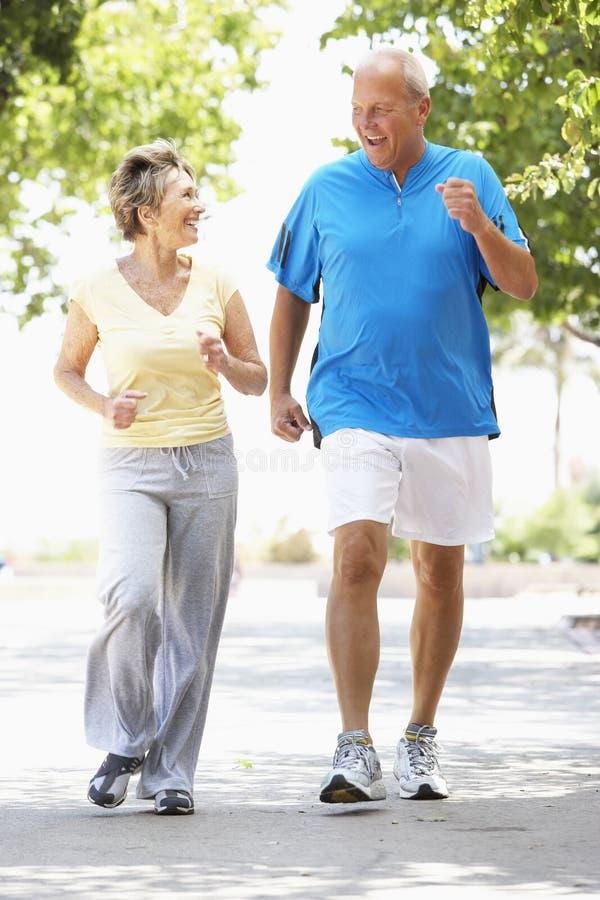 Senior Couple Jogging In Park Stock Photo