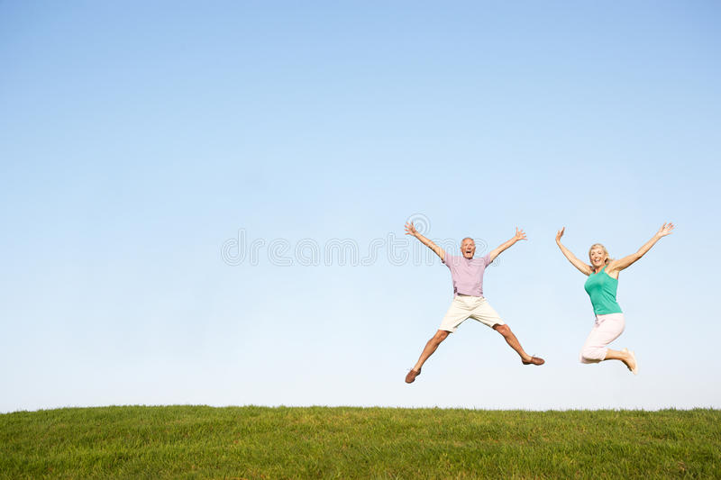 Senior couple jumping in air stock photo