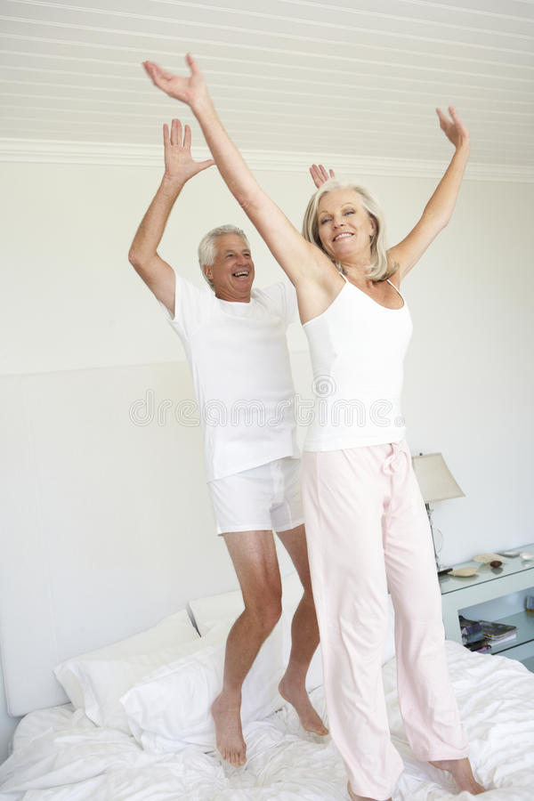 Senior Couple Jumping On Bed royalty free stock photo