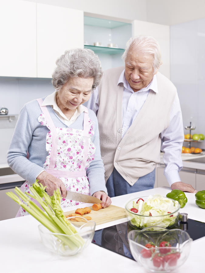 Senior couple in kitchen. Senior asian couple preparing meal together in kitchen