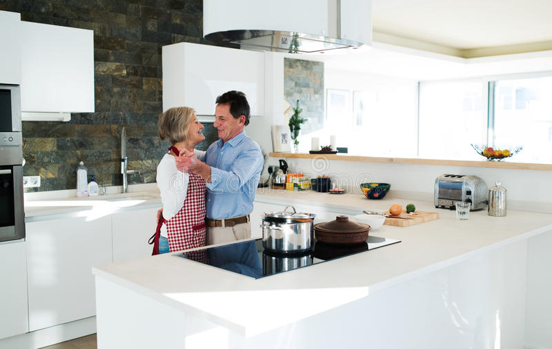 Senior couple in the kitchen cooking and dancing together. royalty free stock photos