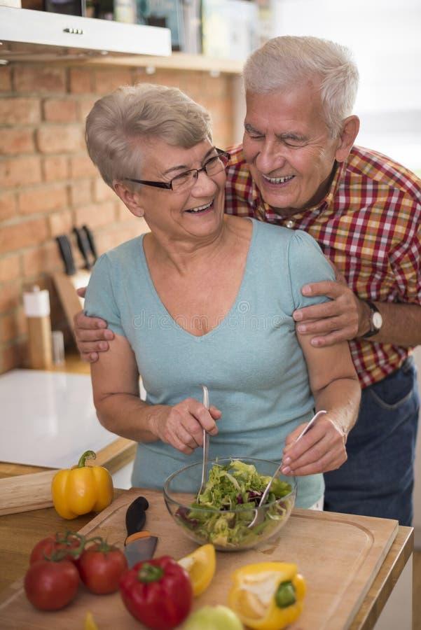 Senior couple at the kitchen. Senior couple preparing fresh salad together stock image