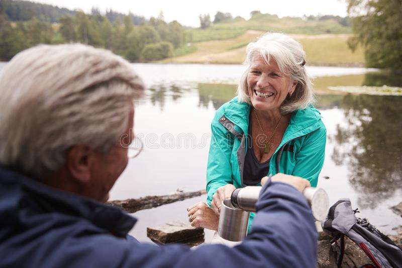 Senior couple by a lake, man pouring coffee to his wife�s cup, over shoulder view, Lake District, UK. Senior couple by a lake, men pouring coffee to his royalty free stock photography