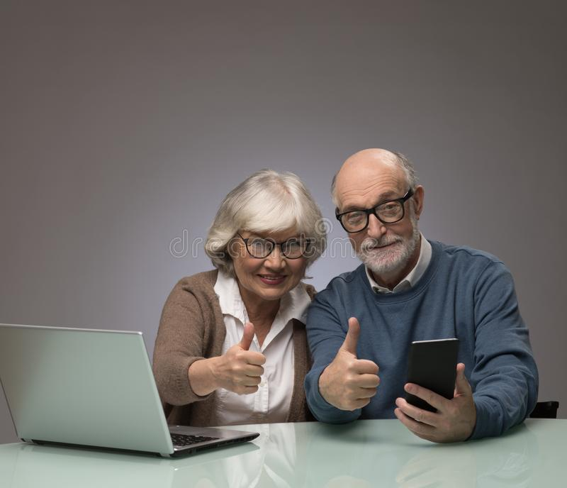 Senior couple with laptop and smartphone stock photos