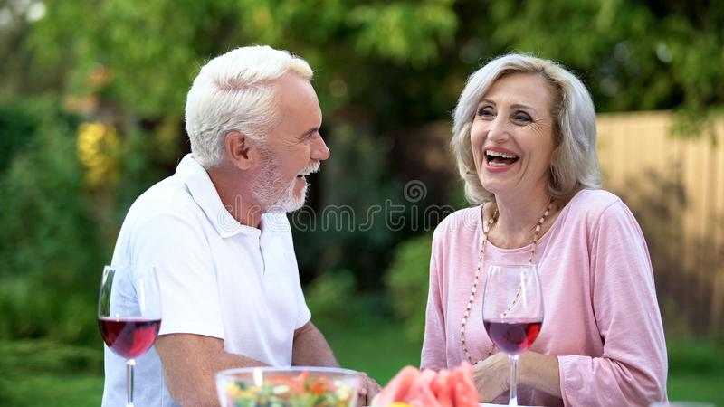 Senior couple laughing at dining table, telling funny jokes, remembering moments stock images