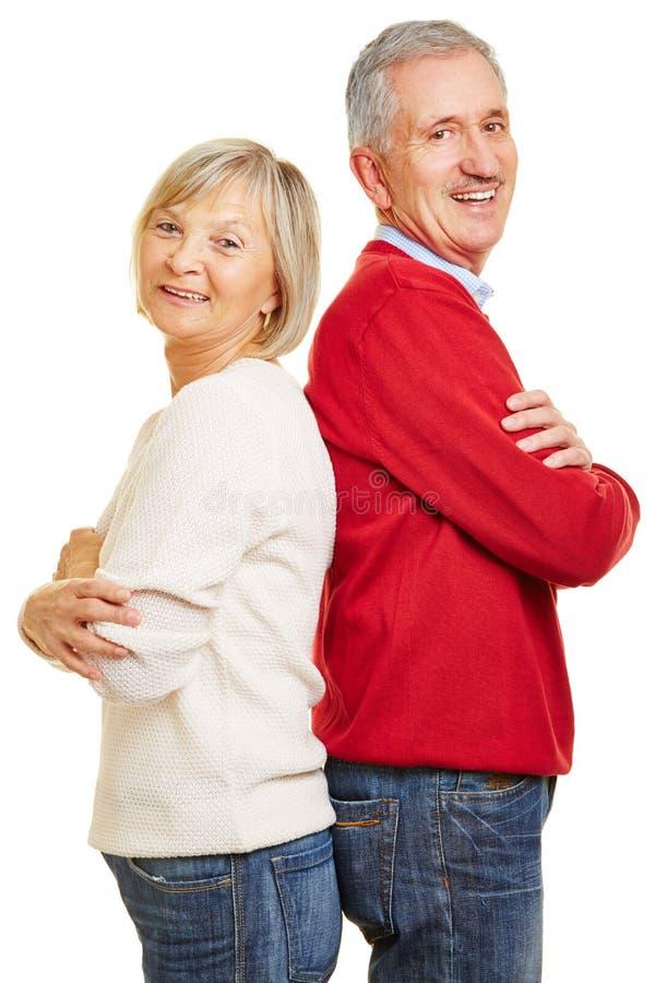 Senior couple leaning back to back stock photography
