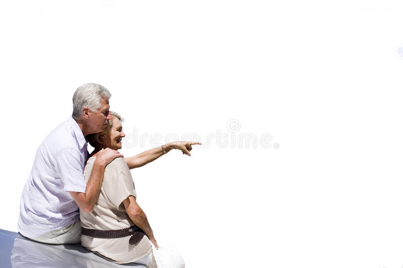 senior couple leaning on car, pointing, cut out royalty free stock photo