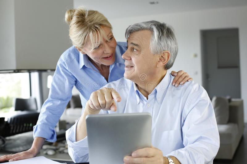 Senior couple looking at bank account on tablet stock photo