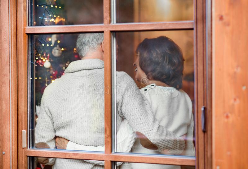 Senior couple looking at Christmas tree at home. stock images