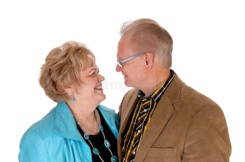 Senior couple looking at each other. A nice seniors' couple standing face to face in closeup and looking at each other, isolated for white background royalty free stock image
