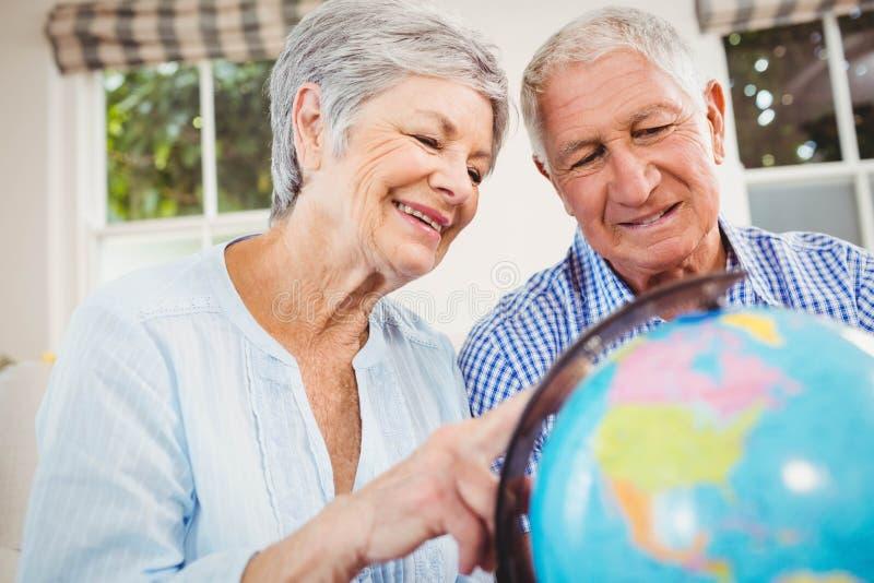 Senior couple looking at a globe stock photo