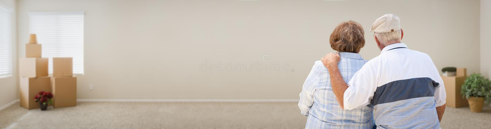 Loving Senior Couple Looking Inside Room with Boxes Banner. royalty free stock photography