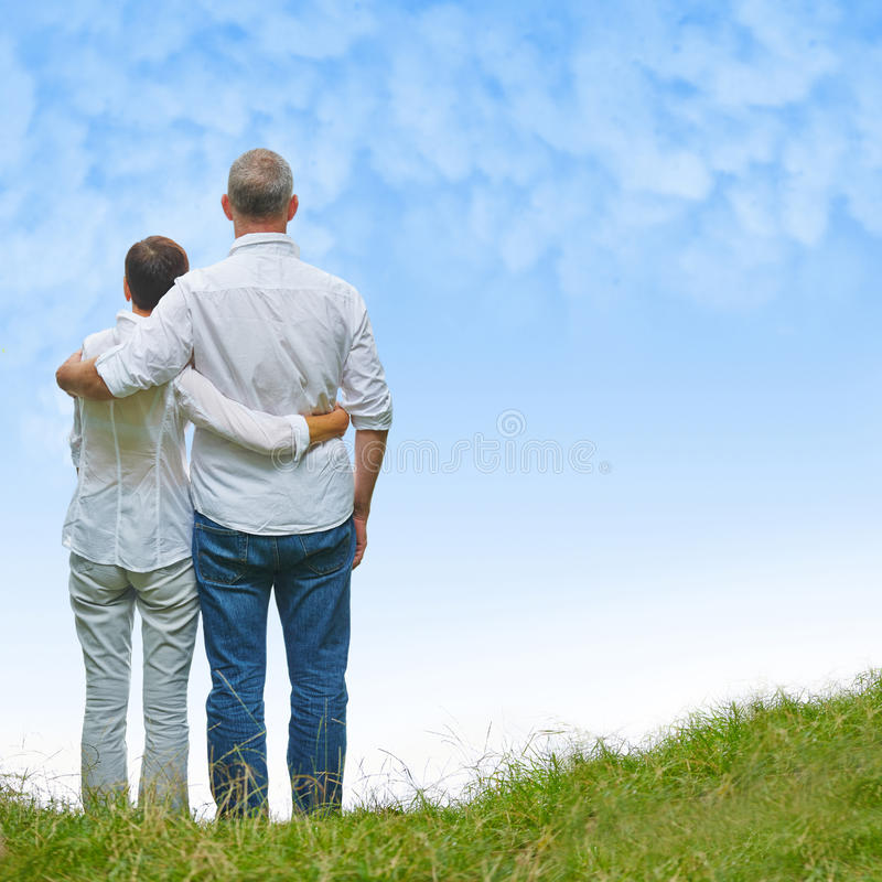Senior couple looking into sky in a hill. Senior couple looking into blue sky in a green hill stock photo