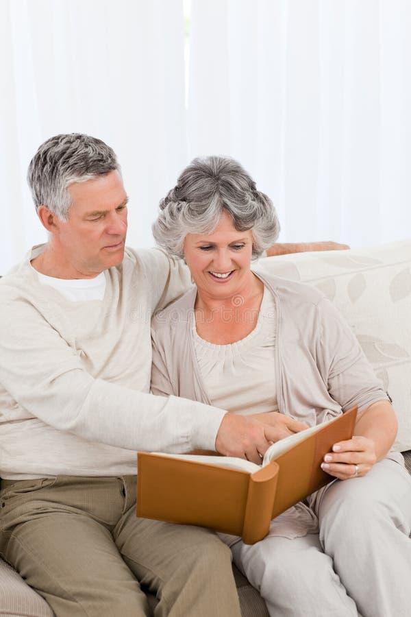 Download Senior Couple Looking At Their Photo Album Stock Photo - Image: 18108610