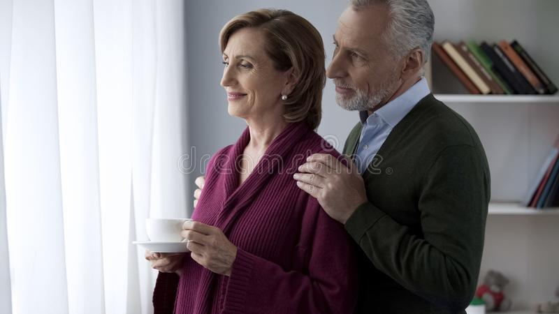 Senior couple looking in window, male hugging lady shoulders from behind, family royalty free stock image