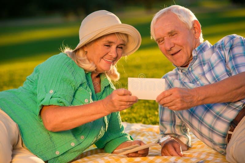 Senior couple looks at photograph. stock image