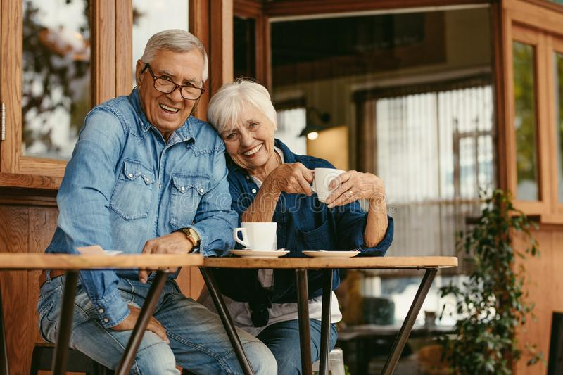 Senior couple in love at coffee shop. Beautiful portrait of old men and women sitting at cafe table with coffee looking at camera royalty free stock photography