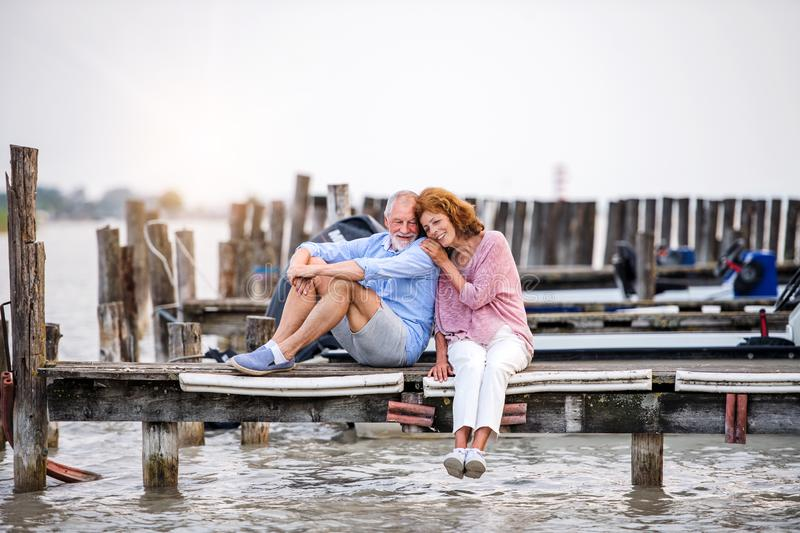 Senior couple on a holiday sitting by the lake, hugging. Senior couple in love on a holiday sitting by the lake, hugging royalty free stock image