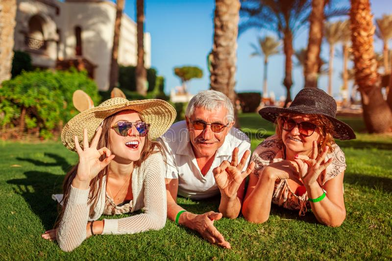 Senior couple lying on grass with adult daughter by hotel. Happy people enjoying vacation. Family values royalty free stock image