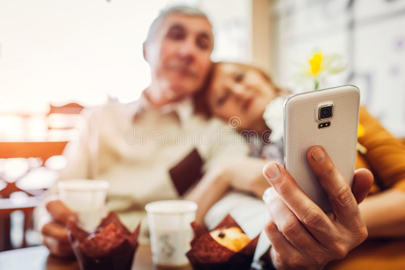 Senior couple makes a selfie using a phone in the cafe. Celebrating anniversary. royalty free stock photography