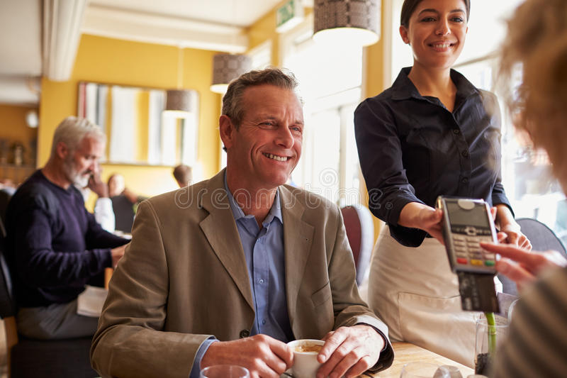 Senior couple making card payment to waitress in restaurant royalty free stock images