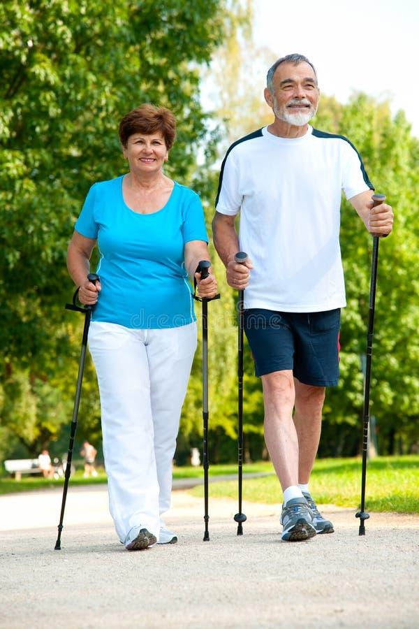 Senior couple making nordic walking stock photos