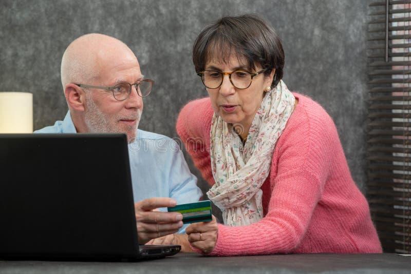 Senior couple making online purchases stock photo