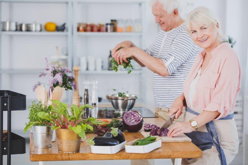 Senior couple making salad royalty free stock images