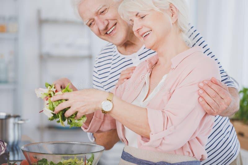 Senior couple making salad stock images