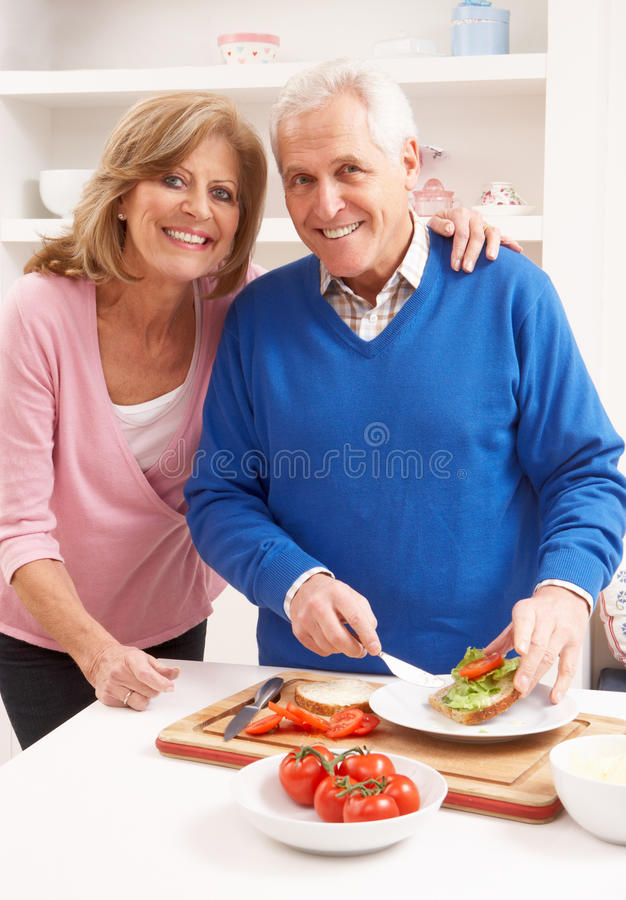 Senior Couple Making Sandwich In Kitchen royalty free stock image