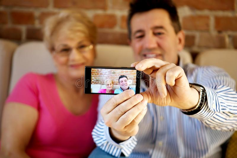 Senior couple making self portrait photo on smartphone. In home stock images