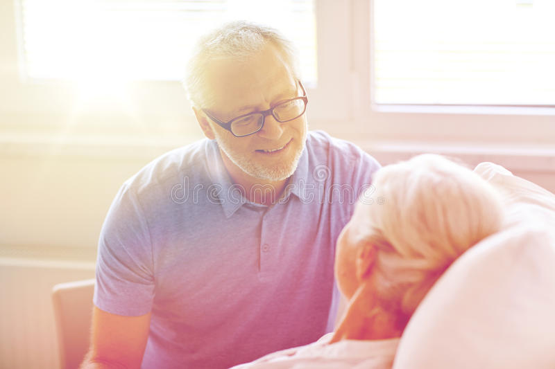 Senior couple meeting at hospital ward. Medicine, age, support, health care and people concept - happy senior men visiting and cheering his women lying in bed at royalty free stock image