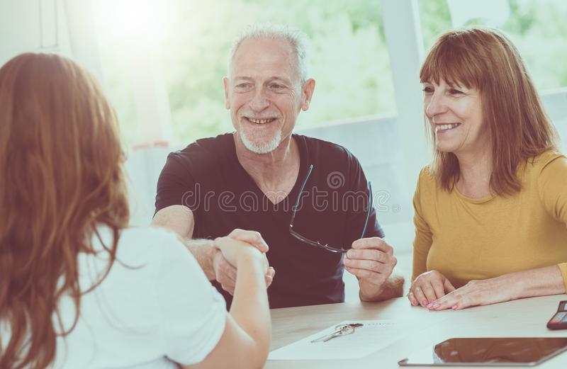 Senior couple meeting real estate agent, light effect stock photography