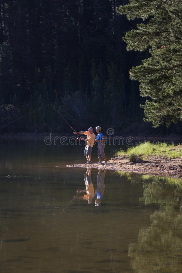 Senior couple, in mid-distance, standing at edge of lake, man fishing, side view. Senior couple, in mid-distance, standing at edge of lake, men fishing, side royalty free stock photo