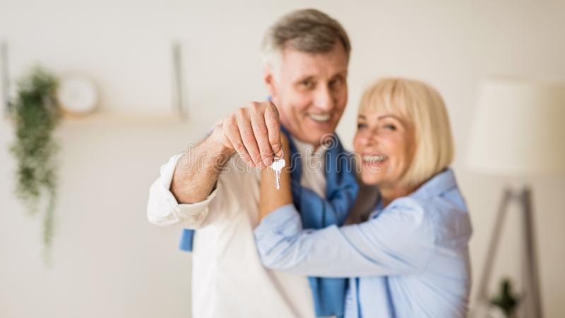 Senior couple moving into new home, man showing keys stock photo