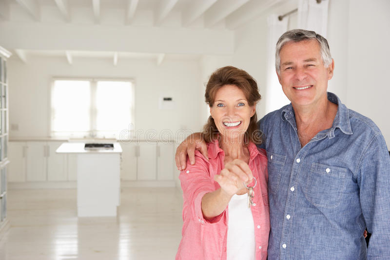 Senior couple in new home. Smiling at camera stock photography