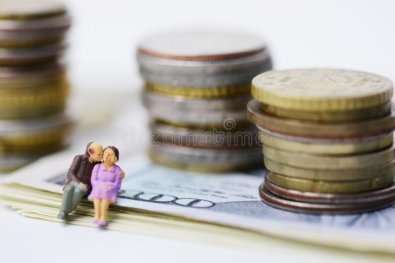 Senior couple with no money shortage, plastic figurine of two old citizens sitting on cash banknotes royalty free stock photo