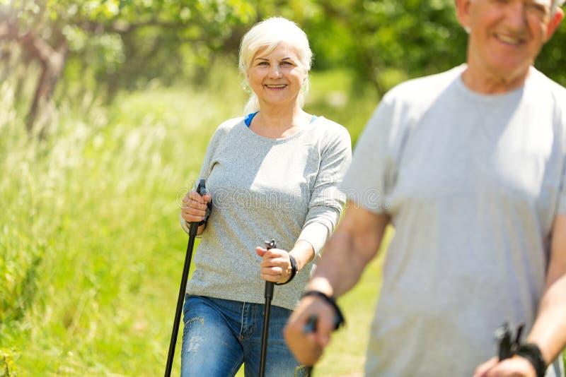 Senior couple nordic walking in park. Smiling happy elderly seniors couple stock photo