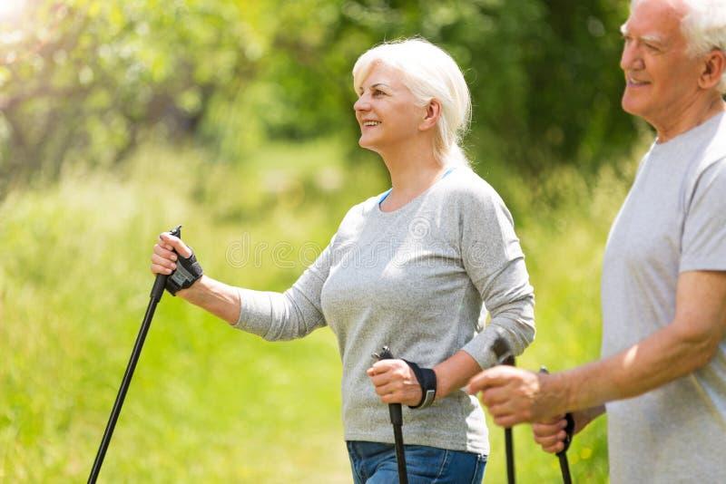 Senior couple nordic walking in park. Smiling happy elderly seniors couple stock photography