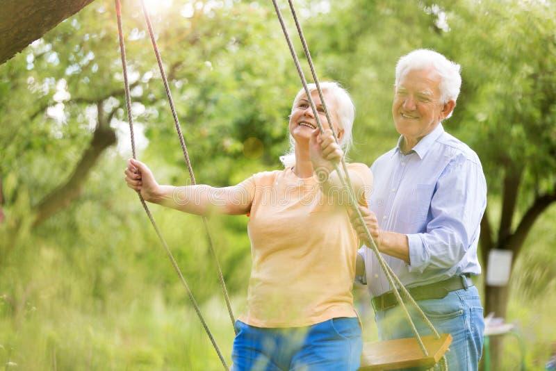 Senior couple outdoors with tree swing. Smiling happy elderly seniors couple royalty free stock image