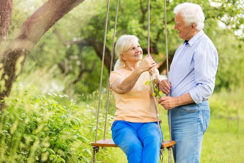 Senior couple outdoors with tree swing. Smiling happy elderly seniors couple stock photography