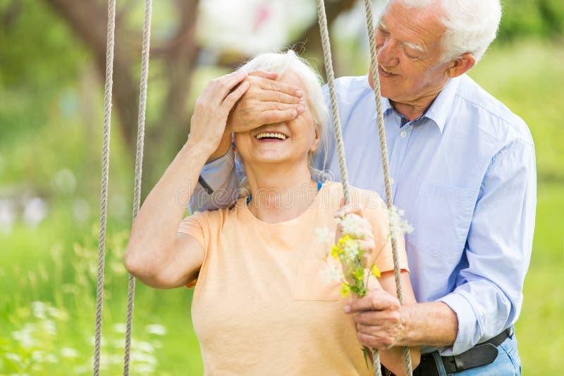 Senior couple outdoors with tree swing. Smiling happy elderly seniors couple stock photo